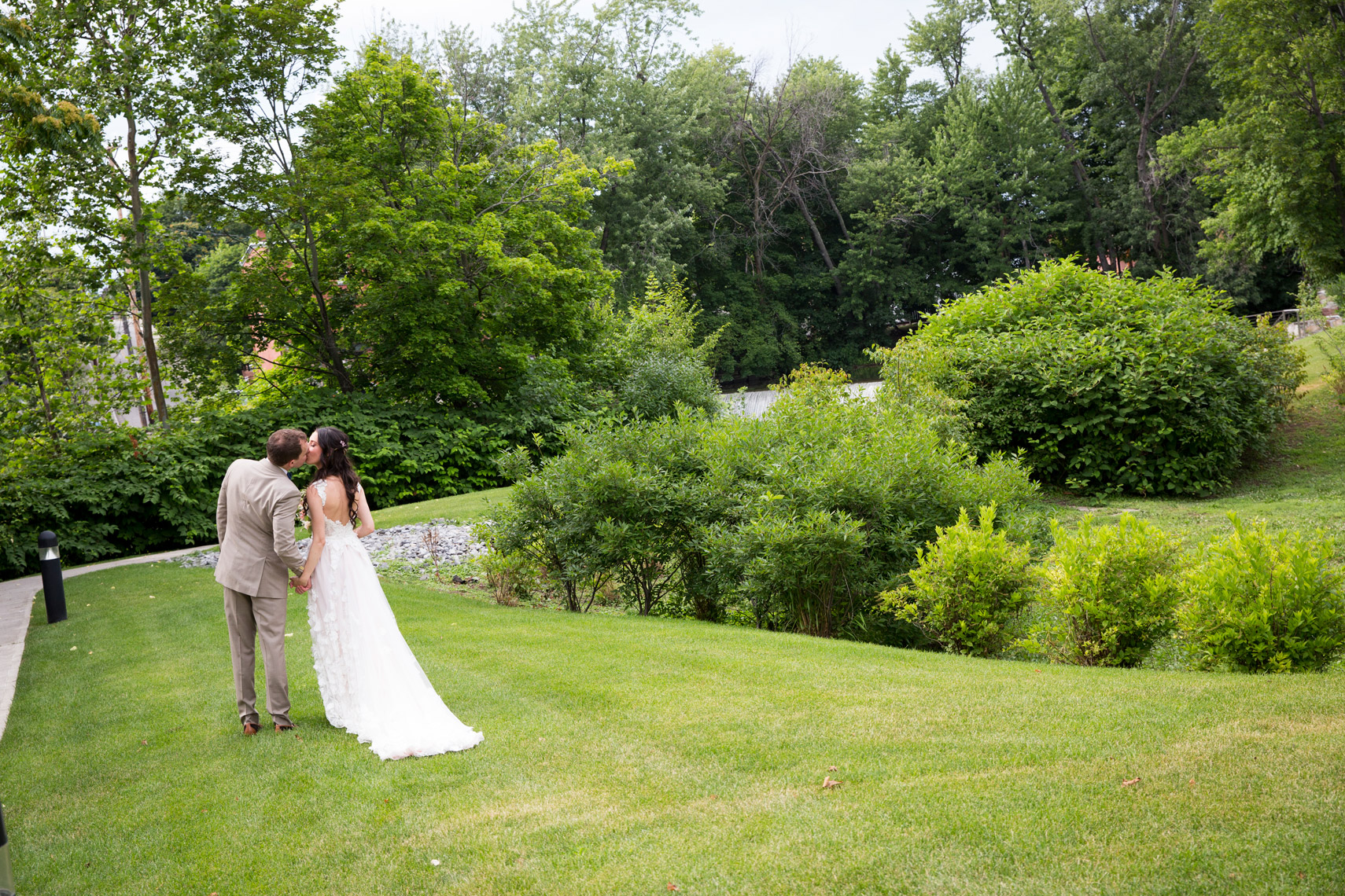 wedding day bride and groom kissing on the lawn at The Roundhouse at Beacon Falls