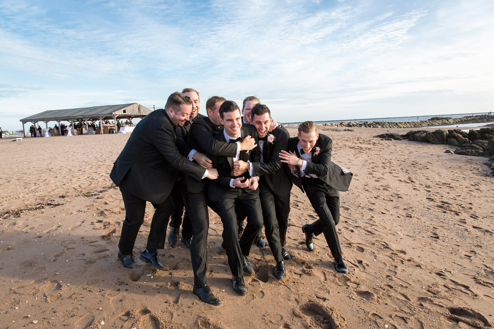 groom-being-tackled-groomsmen-beach-Carousel-Lighthouse-Point-CT-sarma-and-co