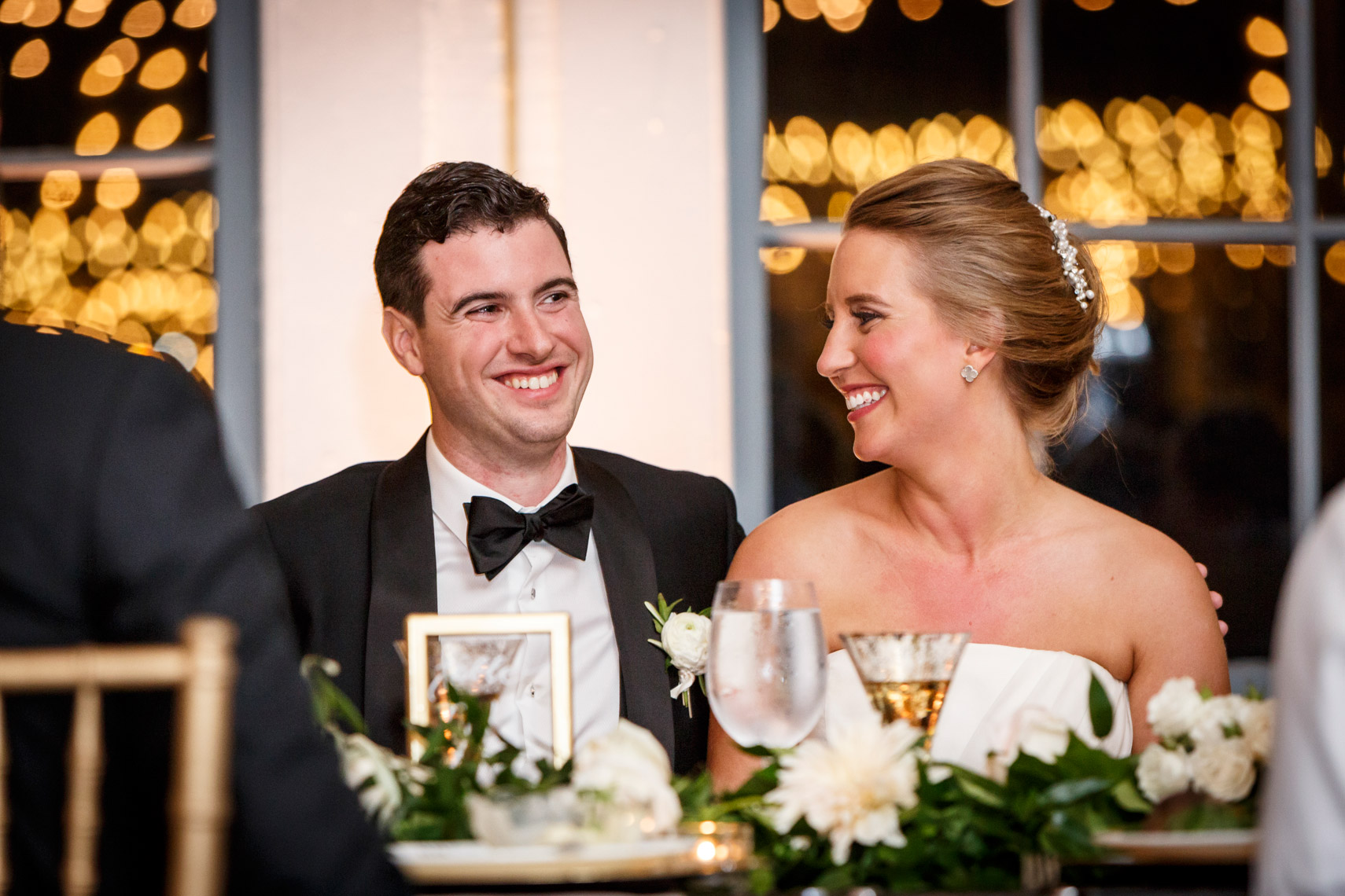 bride-groom-smiling-toasts-reception-Carousel-at-Lighthouse-Point-CT-sarma-and-co
